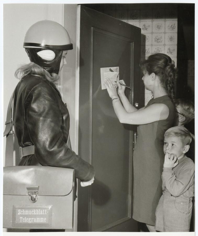 Telegramm- und Eilzustellerin der Deutschen Bundepost in Dienstkleidung mit Zustelltasche bei der Haustürzustellung eines Einschrteibbriefes