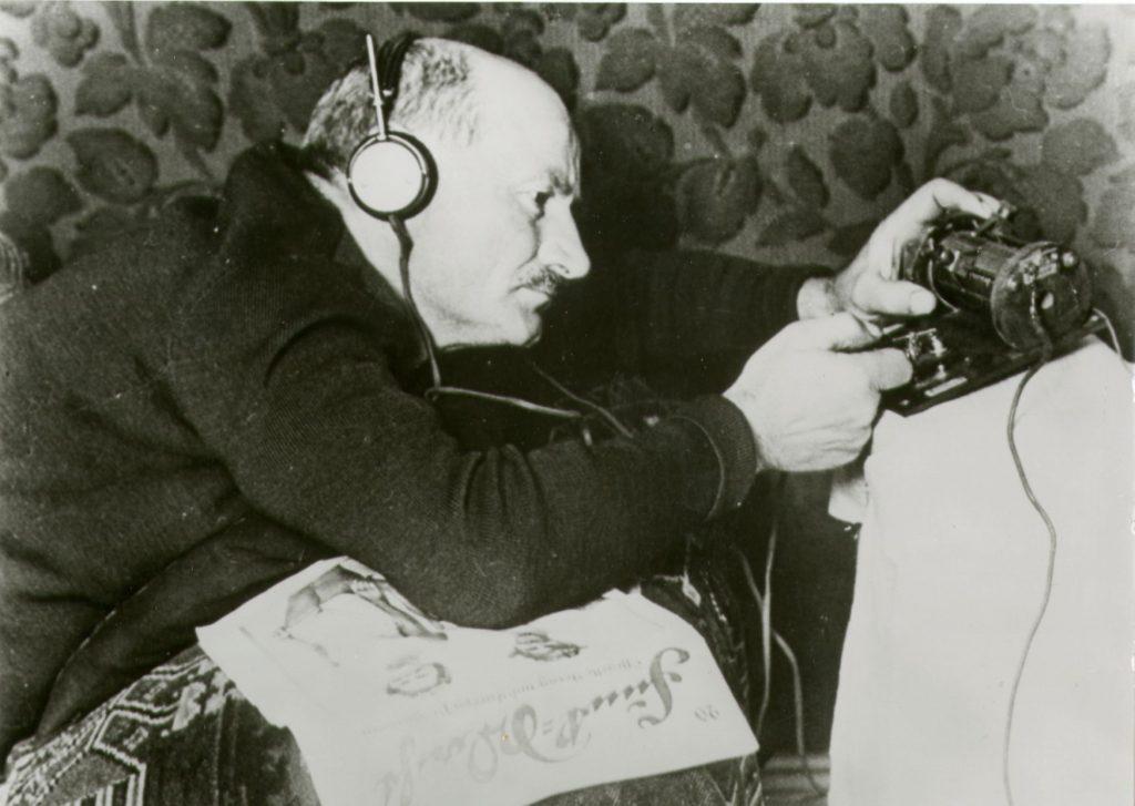 """Mann beim Radio hören mit einen Detekorempfänger nach dem Studium der Rundfunkzeitschrift """"Funk-Stunde"""""""